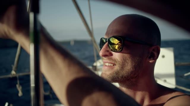 vídeos y material grabado en eventos de stock de hombre dirige el yate - equipo de vela