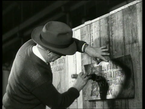 B/W man stenciling label onto side of wooden crate / Ford factory / SOUND