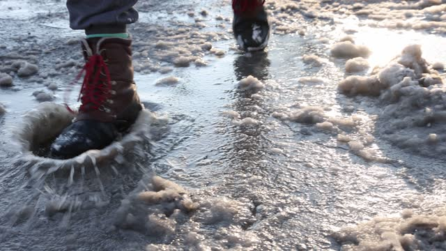 man stepping in slush walking towards camera in a 4k resolution video - stepping stock videos & royalty-free footage