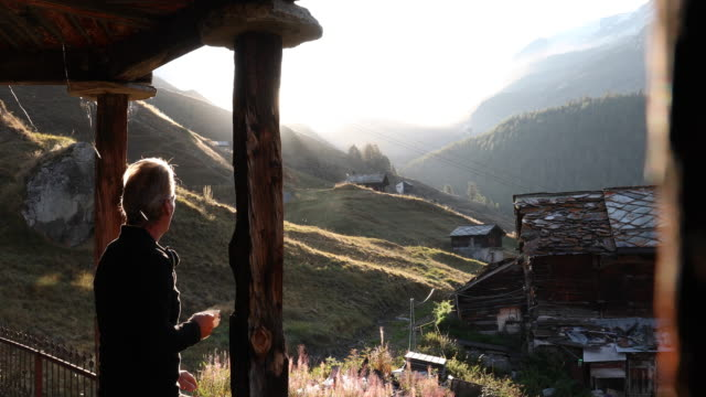 man steps onto chalet veranda with hot drink - chalet video stock e b–roll