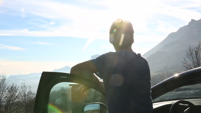 Man steps out of car, looks across to sunrise over mountains
