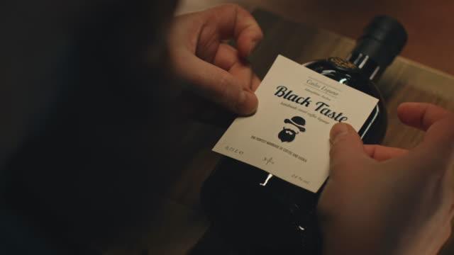 vídeos de stock, filmes e b-roll de homem que fura a etiqueta no licor de café na fábrica - etiqueta mensagem
