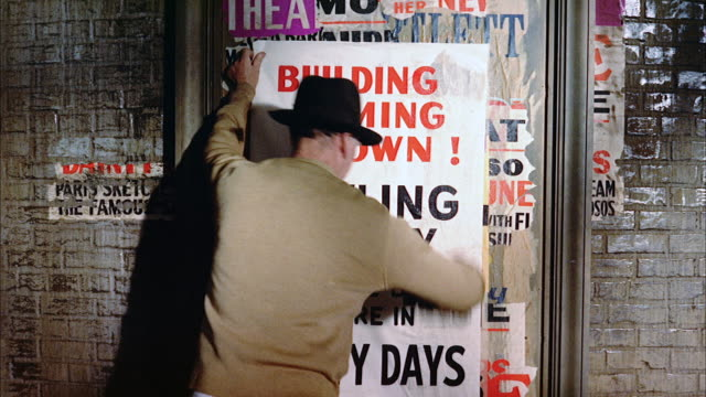 ms man sticking poster on billboard  - poster stock-videos und b-roll-filmmaterial