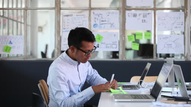 Man sticking postit on window in creative office