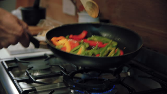man stirring bell peppers - stove stock videos & royalty-free footage