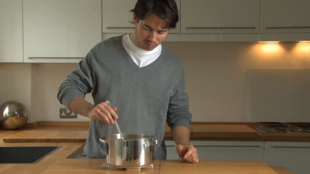 Man stirring spaghetti in pan, UK