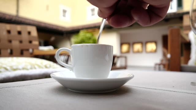 man stirring sugar in coffee cup - tasse oder becher stock-videos und b-roll-filmmaterial