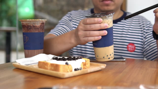 Man Stirring tasty taiwanese popular drink tapioca pearl bubble milk tea.