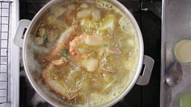 slo mo:トングを使ってエビでトムヤムスープをかき混ぜる男。 - スープ点の映像素材/bロール