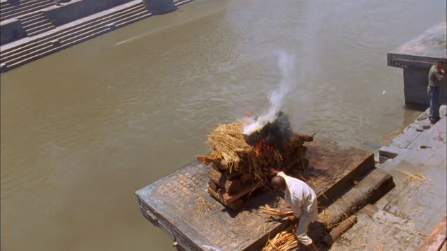 A man stokes a fire under a body on a funeral pyre. Available in HD.
