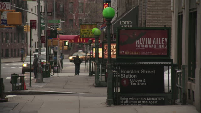 Man stops to glance at a store front on the sidewalk near houston street in new york city in front of the 1 train to uptown and the bronx with advertisements for Alvin Ailey and New Years Eve the movie visible