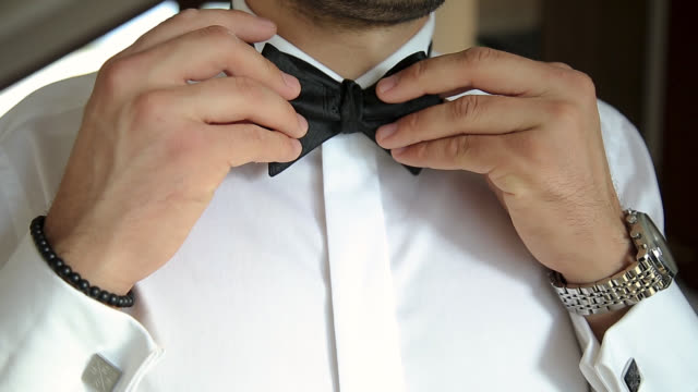 man straightens his bow tie on white shirt - shirt stock videos & royalty-free footage