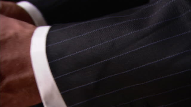 a man straightens his shirt cuffs and pinstripe suit sleeves. - pinstripe stock videos & royalty-free footage