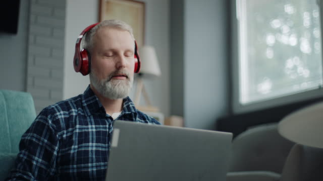 man streams music from laptop to headphones - only mature men video stock e b–roll