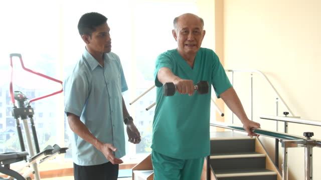 stockvideo's en b-roll-footage met man sterkte opleiding in revalidatie-gym - 70 79 jaar