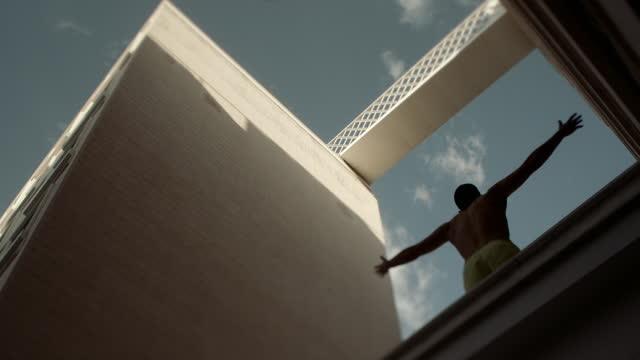 vidéos et rushes de las man stretches arms out wide on modern building - architecture