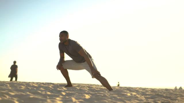 Man stretching legs on sandy beach against sky