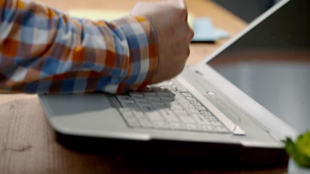 slo-mo-mann fällt einen laptop mit der faust und es schüttelt und fällt über - zerstört stock-videos und b-roll-filmmaterial