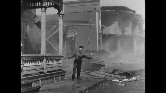 vídeos de stock, filmes e b-roll de 1928 man (buster keaton) struggles against the wind - sorte