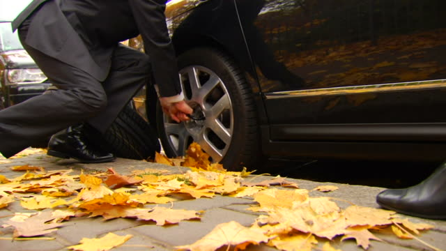 Man Struggles to Remove Tire - Wife Approaches