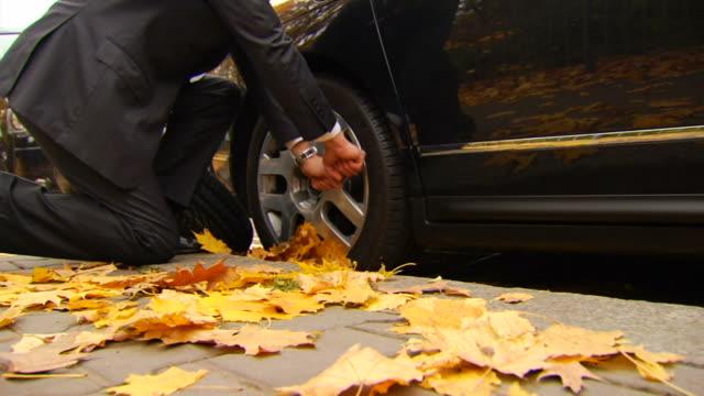 Man Struggles to Unbolt Tire