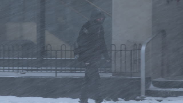 A man struggles to walk in heavy snow and powerful winds during an intense blizzard in Waterbury Connecticut