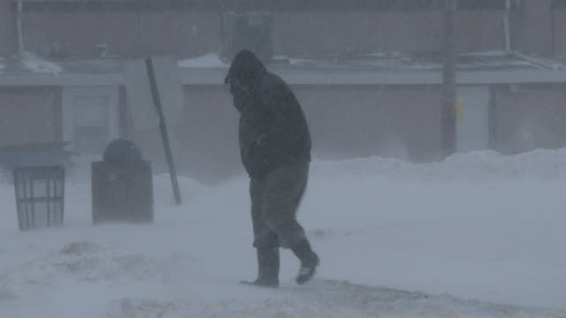 a man struggles to walk in near whiteout conditions along the jersey shore as strong winds batter him during the height of the blizzard of 2016 - gale stock videos and b-roll footage