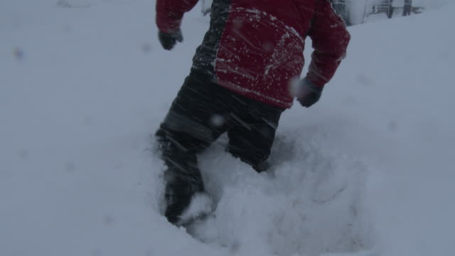 a man struggles to walk in waist deep snow in adams new york during a lake effect storm that dumped over five feet of snow on the area - scott mcpartland stock videos & royalty-free footage
