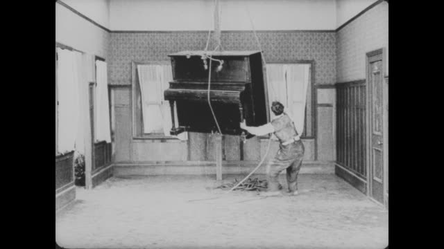 1920 man (buster keaton) struggles while hoisting a piano into the house, ultimately breaking it - hoisting stock videos & royalty-free footage