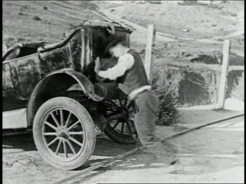 b/w 1925 man (billy bevan) struggling to push stuck car / feature - 1925 stock videos & royalty-free footage