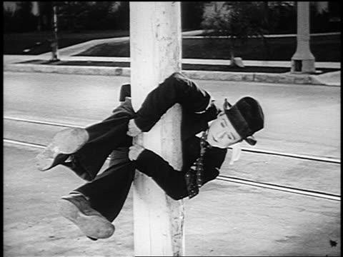 b/w 1926 man (harry langdon) stuck clinging midway on pole in street - 1926 stock-videos und b-roll-filmmaterial