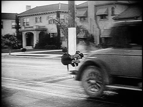 vídeos y material grabado en eventos de stock de b/w 1926 man (harry langdon) stuck midway on pole in street after two cars pass - 1926