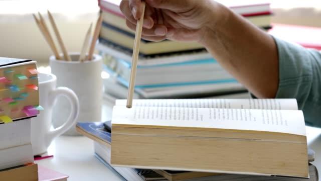vidéos et rushes de homme étudiant et lisant un livre - effort
