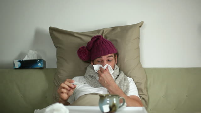 MS Man suffering from cold and flu, checking thermometer / Potsdam, Brandenburg, Germany