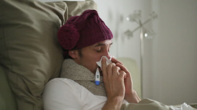 cu man suffering from cold and flu, holding thermometer in mouth / potsdam, brandenburg, germany - erkältung und grippe stock-videos und b-roll-filmmaterial