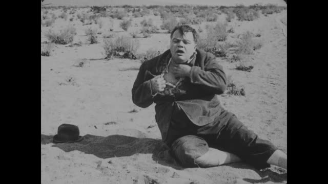 vídeos y material grabado en eventos de stock de 1918 man (fatty arbuckle), suffering from thirst, spits cotton and sees a mirage - sediento