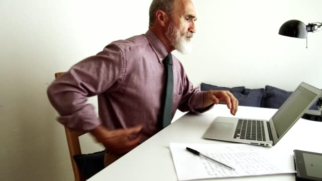 man suffering of back pain at the computer - postura video stock e b–roll