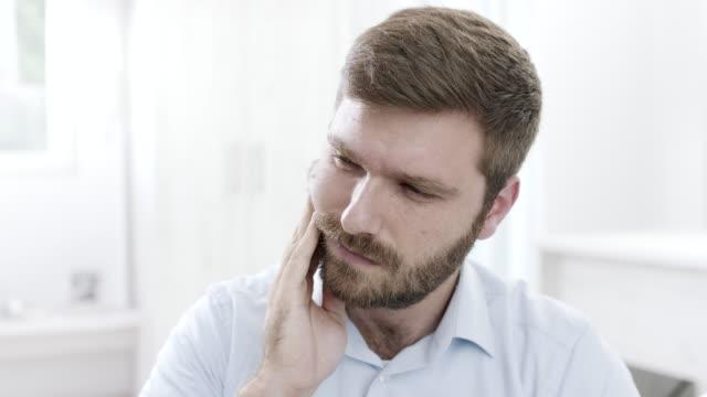 vídeos de stock e filmes b-roll de man suffering tooth pain - dente humano