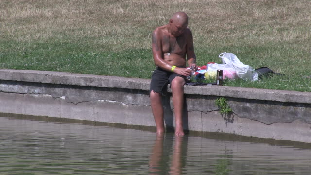 vidéos et rushes de man sunbathes near a man made lake in the pole mokotowskie park in central warsaw, poland on june 24, 2019. poland has been suffering from a sudden... - varsovie