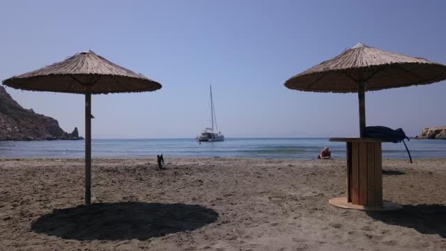 男がビーチではだし、入り江で泳ぐ女性 - 中年の男性だけ点の映像素材/bロール