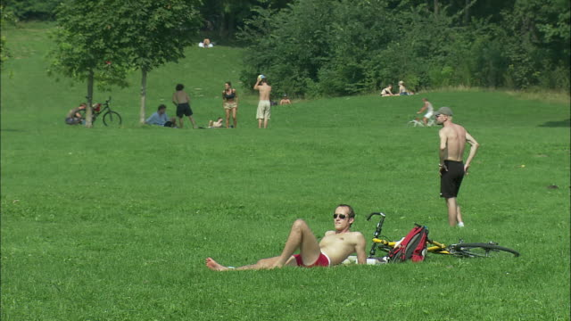 ws man sunbathing on lawn in englischer garten (english garden), munich, bavaria, germany - 2002 stock-videos und b-roll-filmmaterial