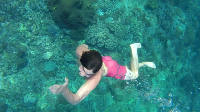 a man surfaces after swimming underwater with a green coral reef under him. - bali stock videos & royalty-free footage