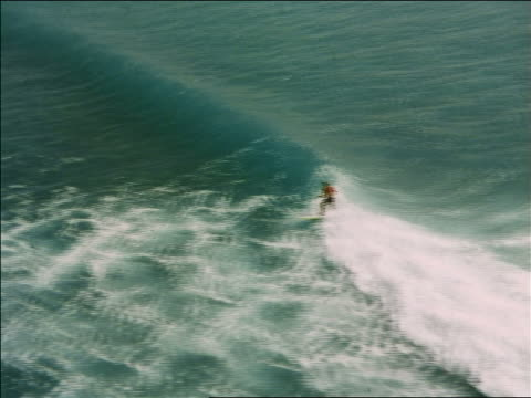 1969 aerial man surfing on wave in ocean / hawaii / travelogue - 1969 stock videos and b-roll footage
