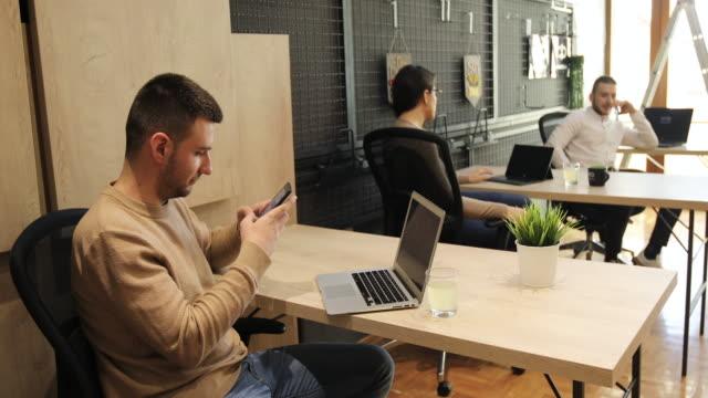 vídeos de stock, filmes e b-roll de homem navegando na rede usando celular no escritório - planta de vaso