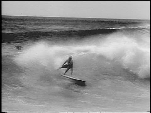 b/w 1966 man surfing towards camera in surfing competition + wipes out in surf / hawaii / newsreel - wipeout stock videos & royalty-free footage