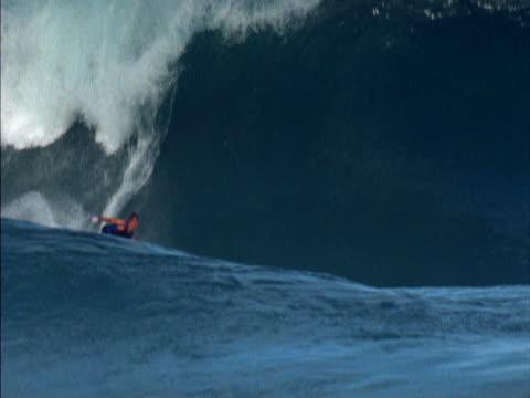 vídeos de stock, filmes e b-roll de man surfs a large wave, the camera tracking him. - grande