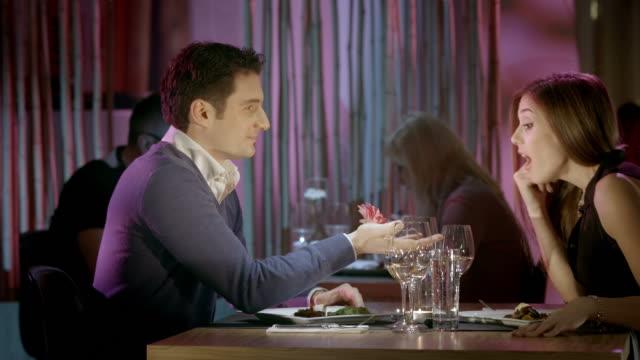 hd :dolly man 驚く女性、花 - お食事デート点の映像素材/bロール