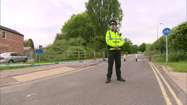 vidéos et rushes de man suspected of murdering family found dead by police england oxfordshire ext police officer and tape across road close to woodland where body of... - oxfordshire