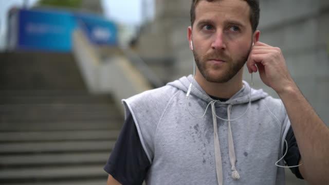 vidéos et rushes de homme la transpiration et de mettre ses écouteurs pour commencer à courir - casque audio