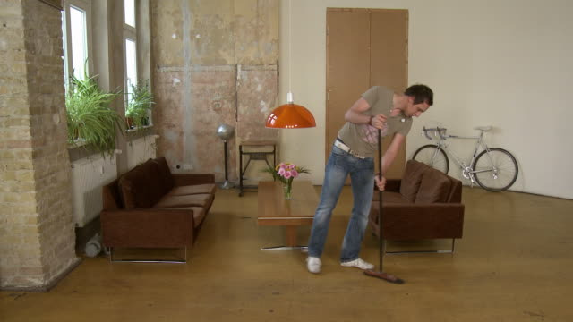 ws man sweeping floor in apartment living room / berlin, germany - housework stock videos and b-roll footage